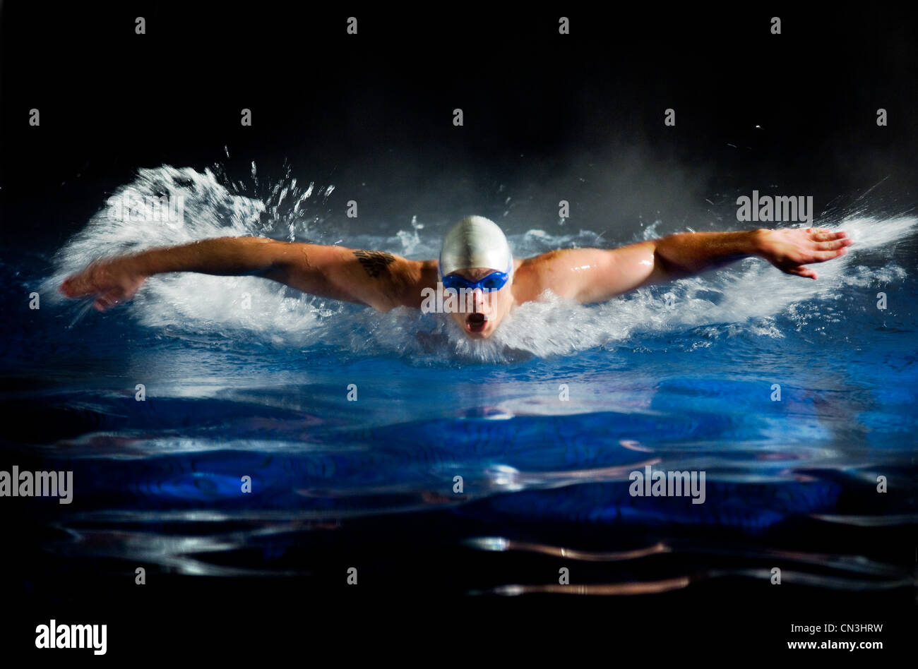 Young man swimming in pool - Stock Image