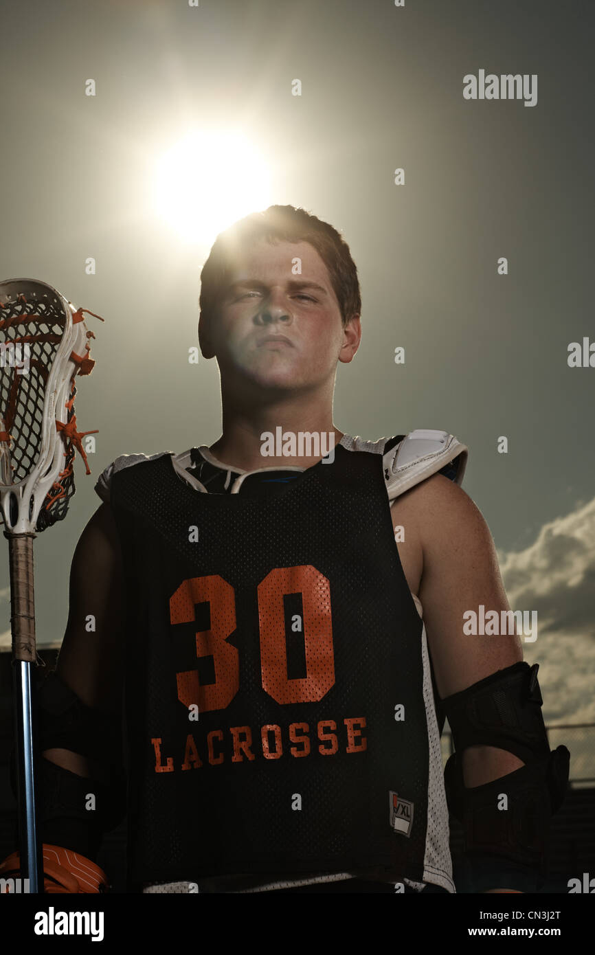 Portrait of young sportsman holding lacrosse stick - Stock Image