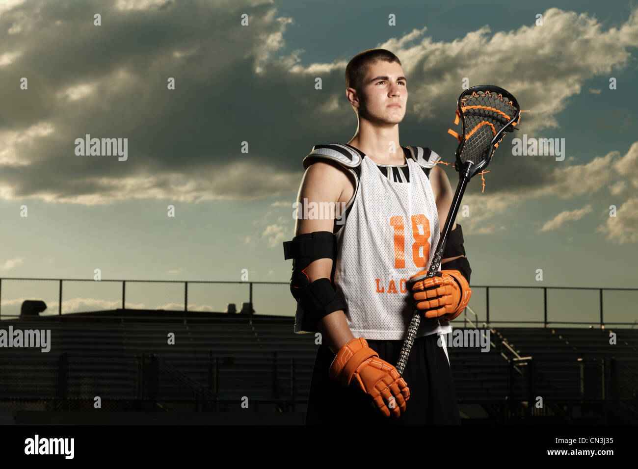 Young sportsman holding lacrosse stick in stadium - Stock Image