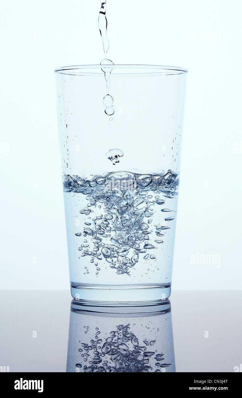 Pouring water into glass - Stock Image