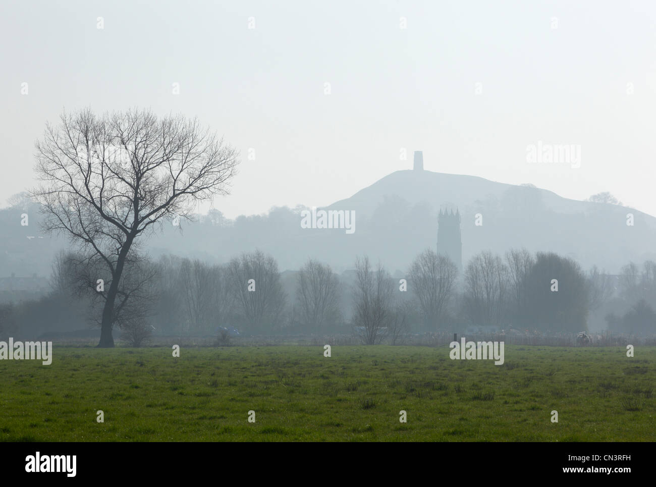 The tower of St John's Church with the ruin of St Michael's Church on Glastonbury Tor in the Distance. Somerset. - Stock Image