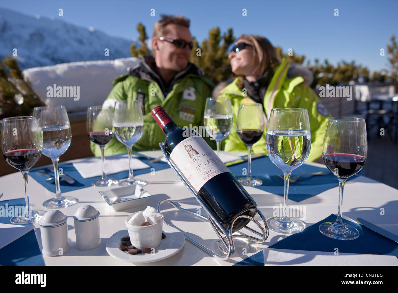 France, Savoie, Méribel, ski slopes of 3 valleys, couple with the winter sports on the terrace of the restaurant - Stock Image