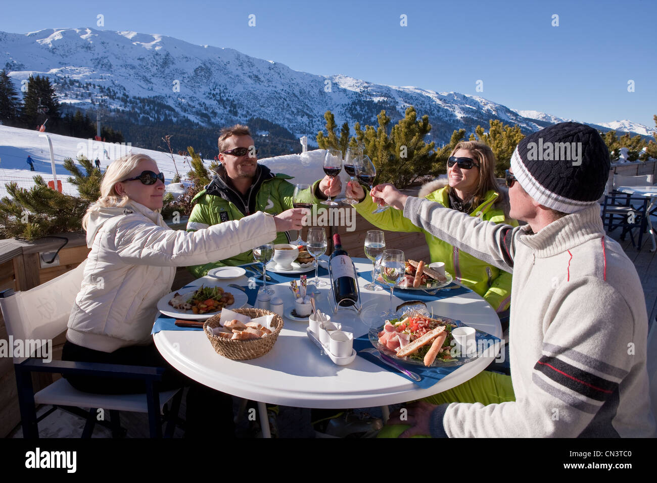 France, Savoie, Méribel, ski slopes of 3 valleys, couples with the winter sports on the terrace of the restaurant - Stock Image