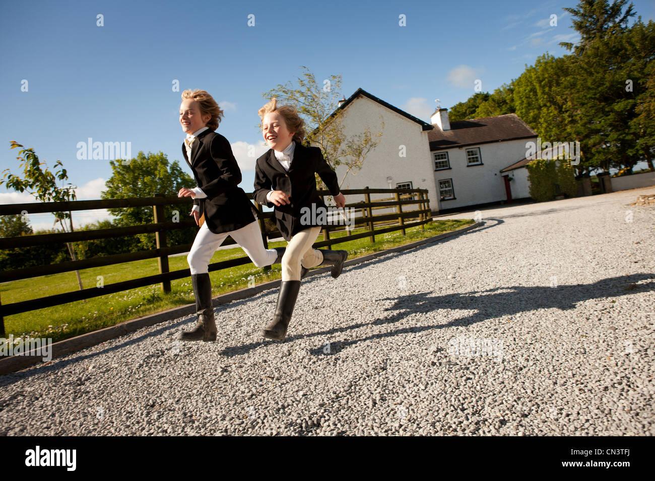 Boys running along gravel path of ranch - Stock Image