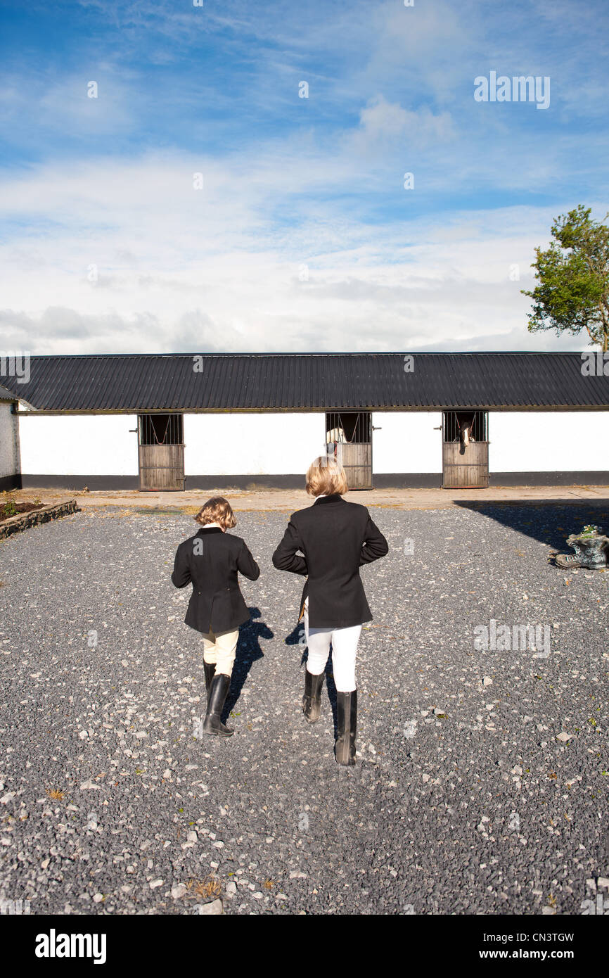 Two boys in riding gear running to stables - Stock Image
