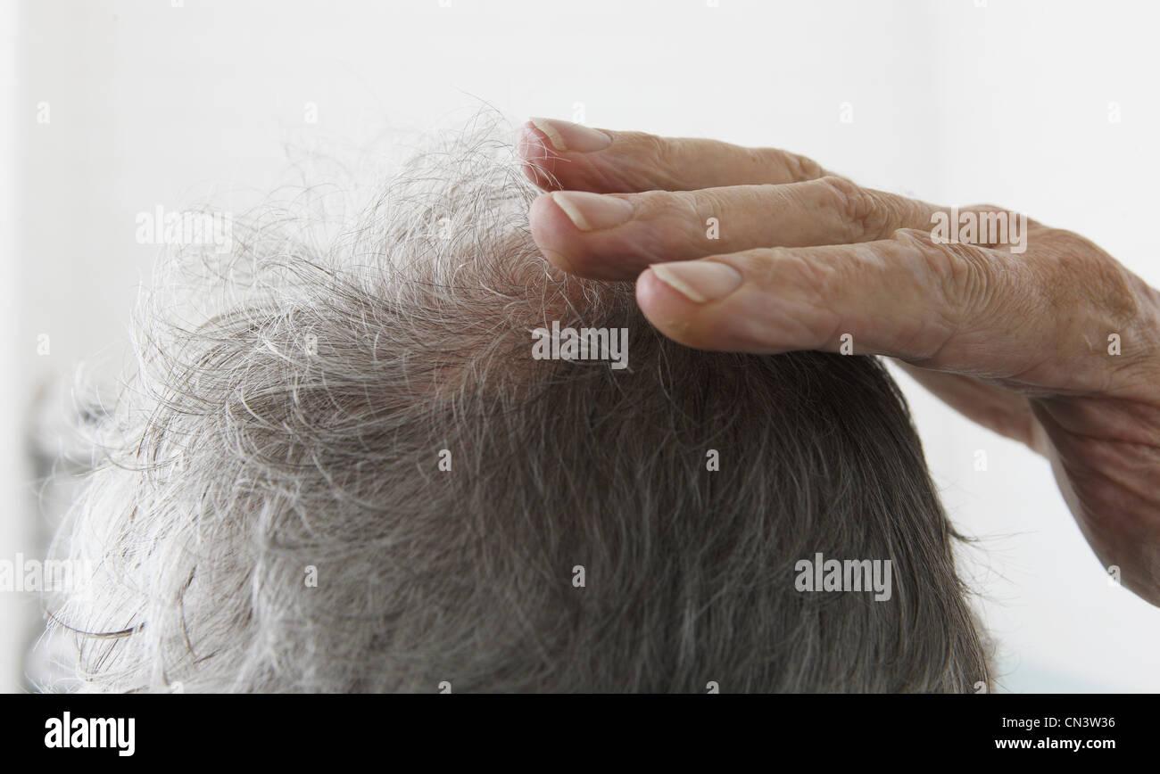 Senior man touching bald spot - Stock Image