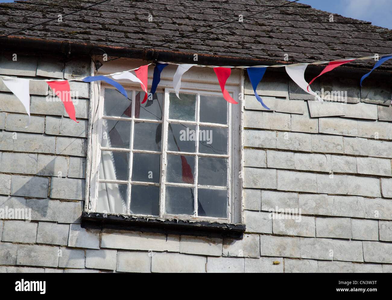 Blue, white and red flags or bunting attached to an old building royal wedding celebration jubilee queen street - Stock Image