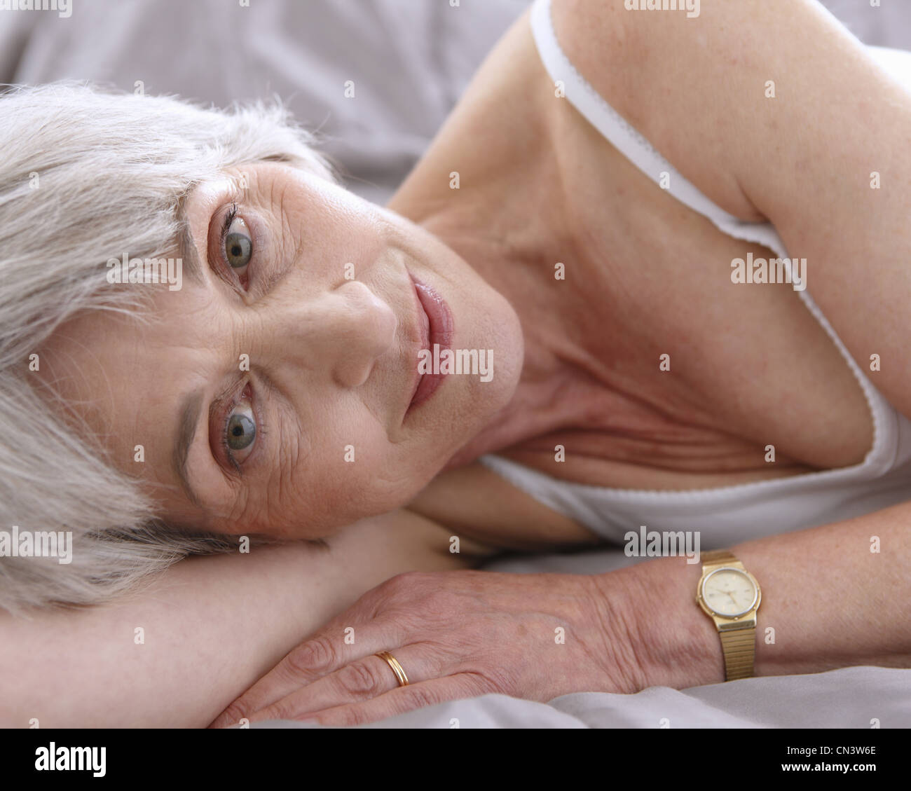 Senior woman relalxing on bed, smiling - Stock Image