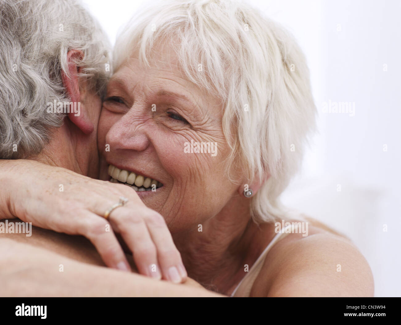 Senior couple embracing, close up - Stock Image