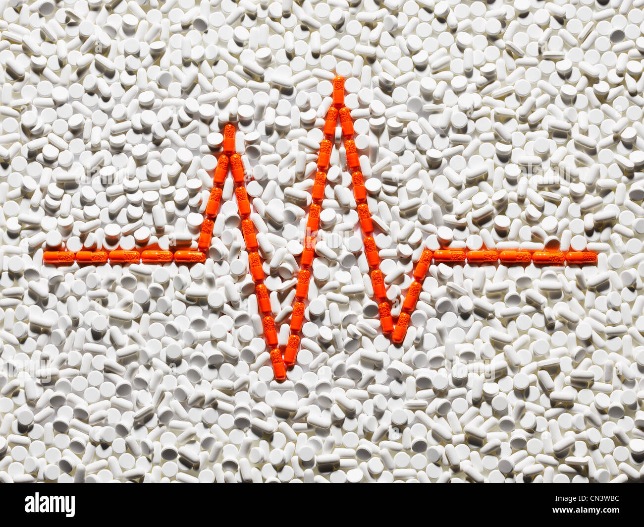 Pulse trace made up of orange pills - Stock Image