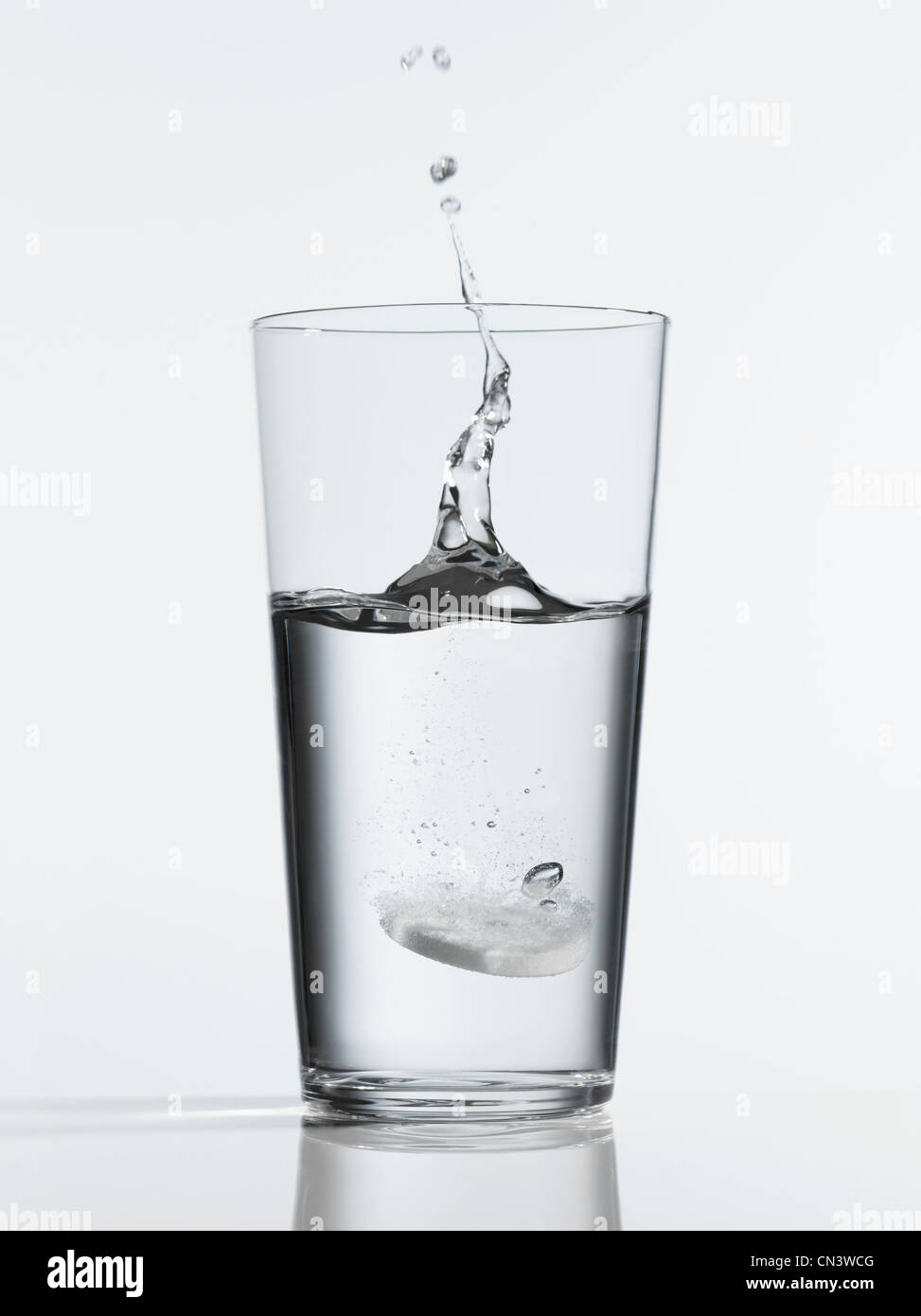 Tablet splashing into glass of water - Stock Image