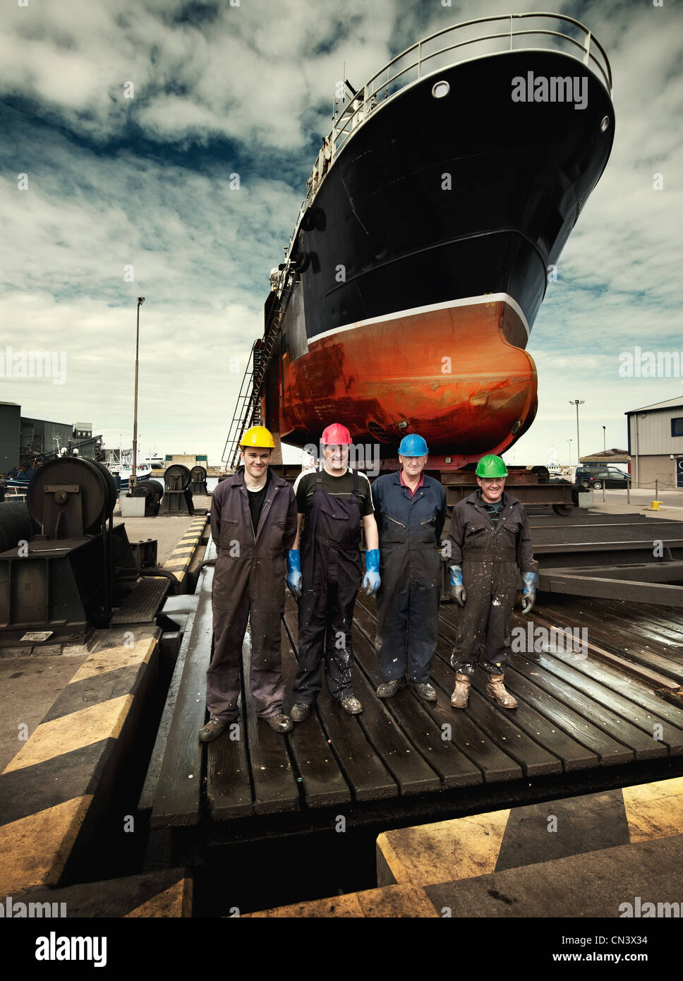Dockers in coloured hard hats in a line - Stock Image
