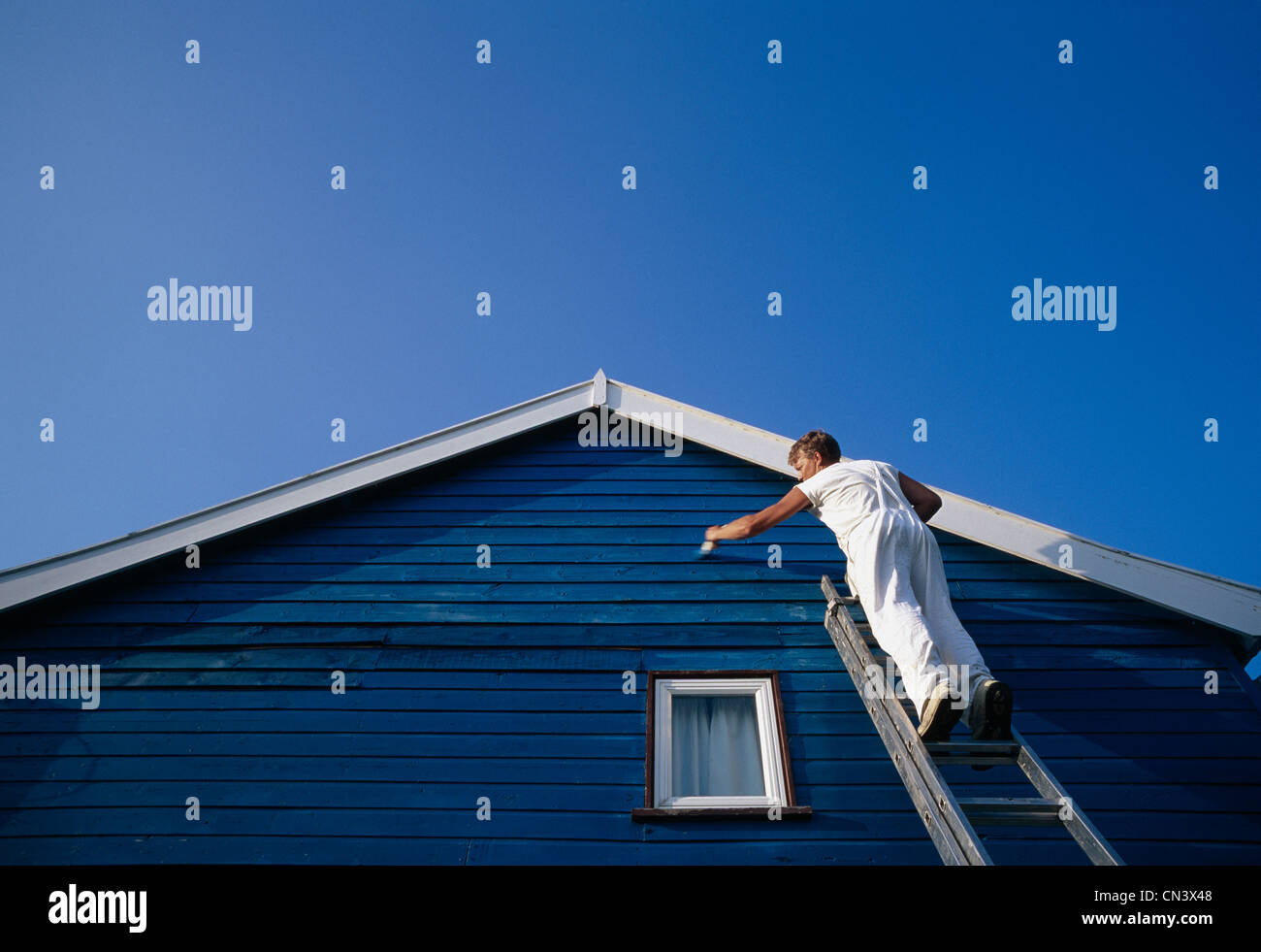 A man painting the weatherboarding of a house Stock Photo
