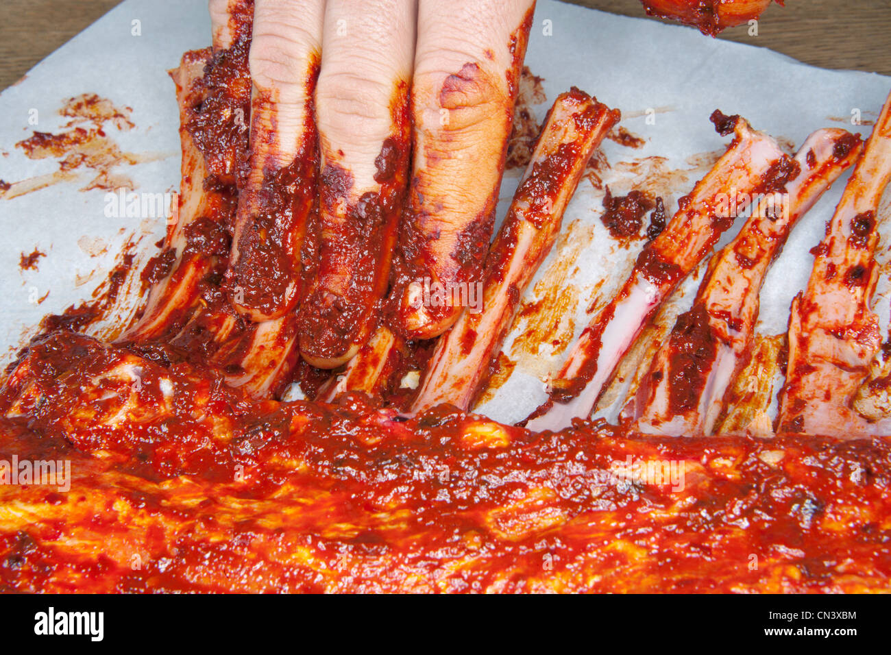 Rubbing marinade over spare ribs - Stock Image