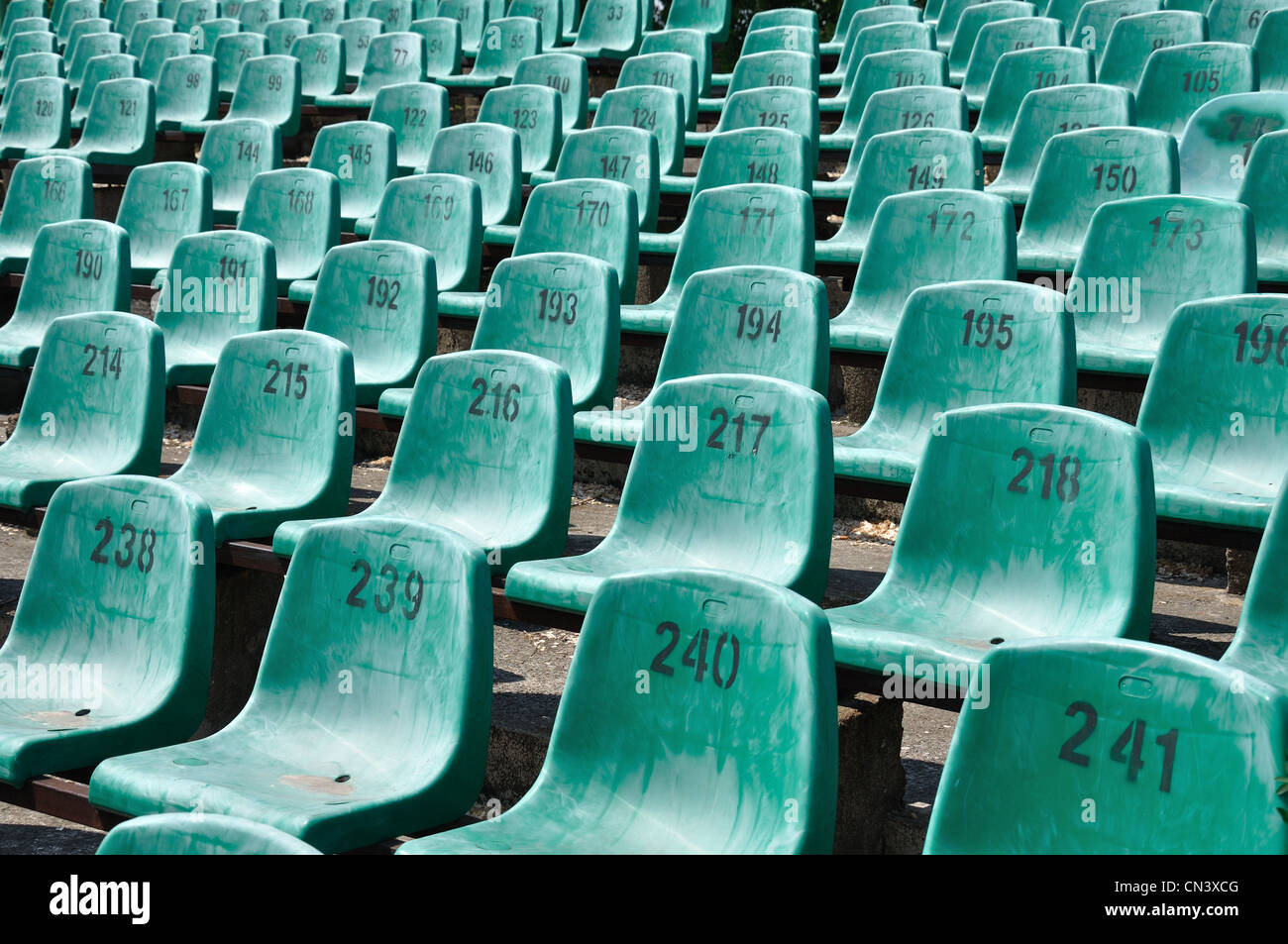 Green numbered seats at a stadium - Stock Image