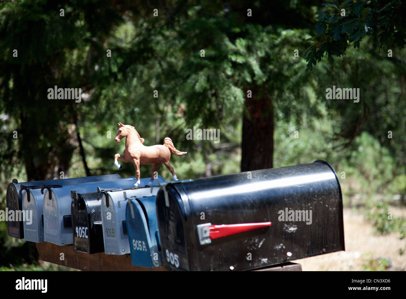 Rural mailboxes with plastic horse figurine - Stock Image