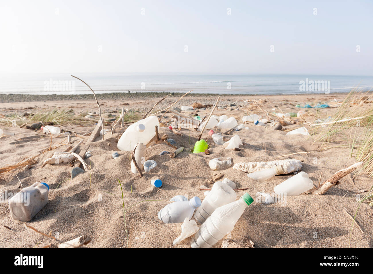 plastic bottles and other rubbish washed up by the tide on a beach - Stock Image