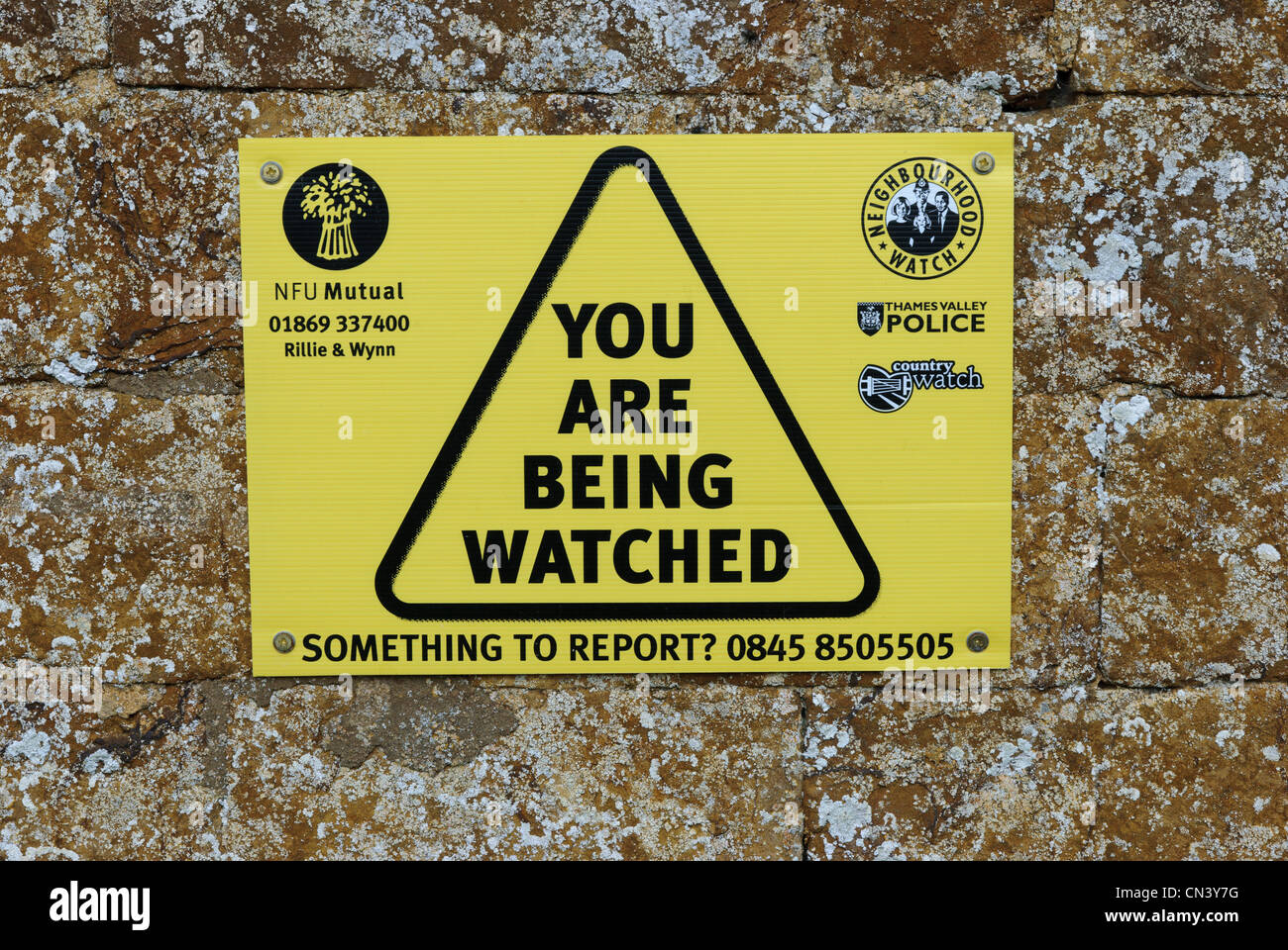 Neighbourhood Watch/Country Watch sign on the wall of St Peter ad Vincula Church in  South Newington, Oxfordshire. - Stock Image