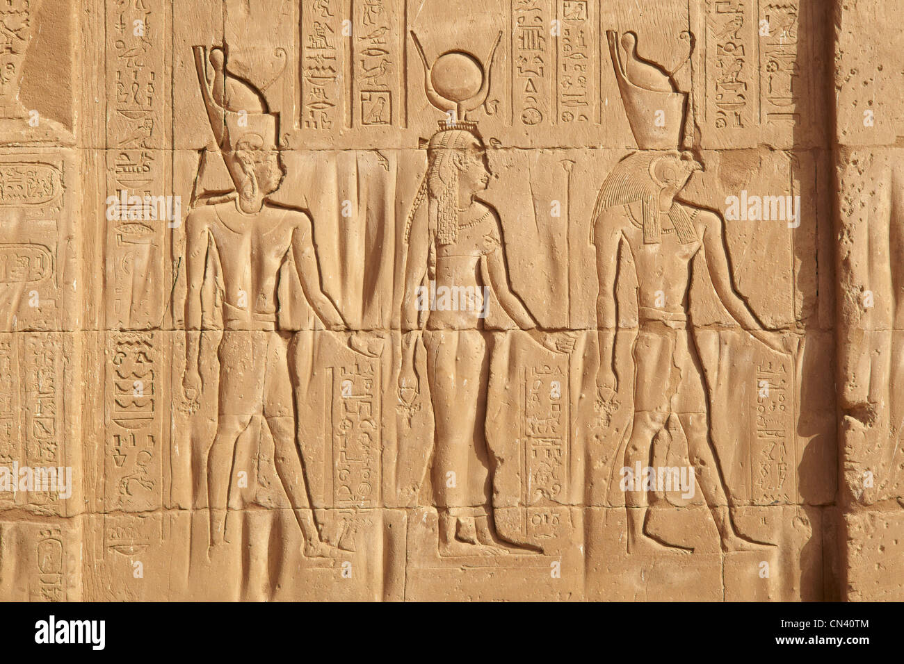 Egypt - Edfu, Temple of Horus, detail, relief of the wall inside the Horus Temple, figures of Horus, Isis and Osiris - Stock Image