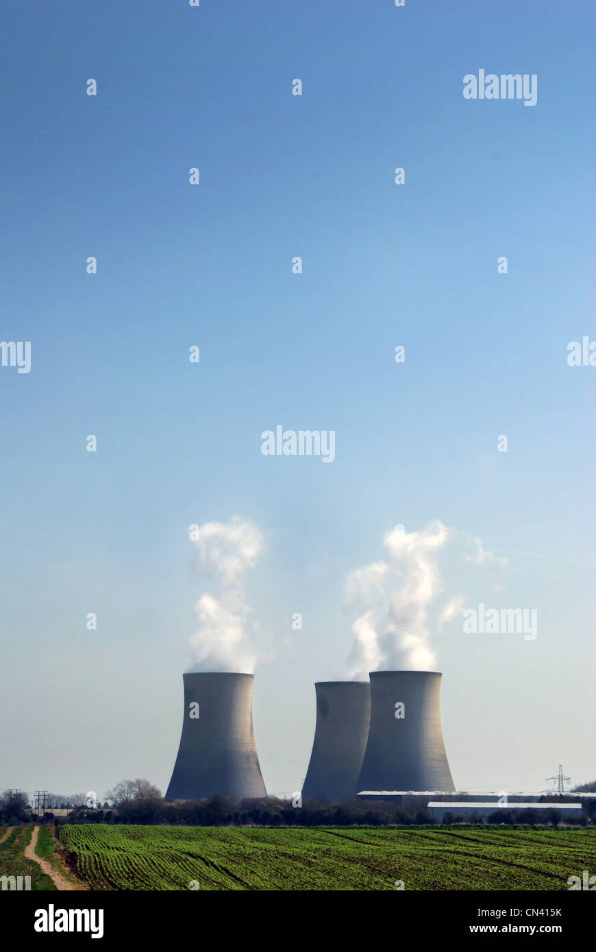 Three cooling towers venting water vapor up into empty blue sky, field in the foreground, nuclear power plant. - Stock Image