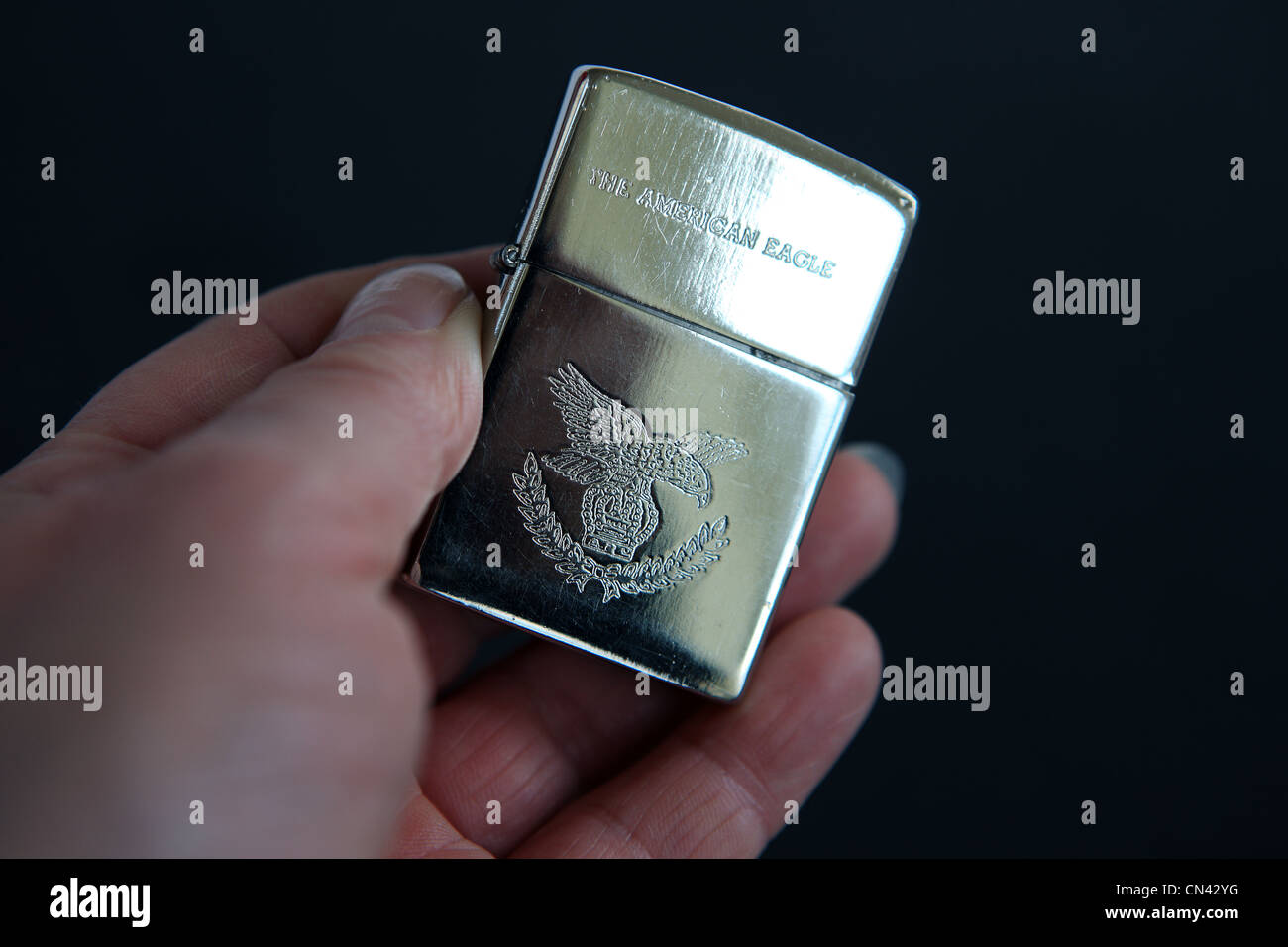 Hand holding a Zippo American Eagle lighter - Stock Image