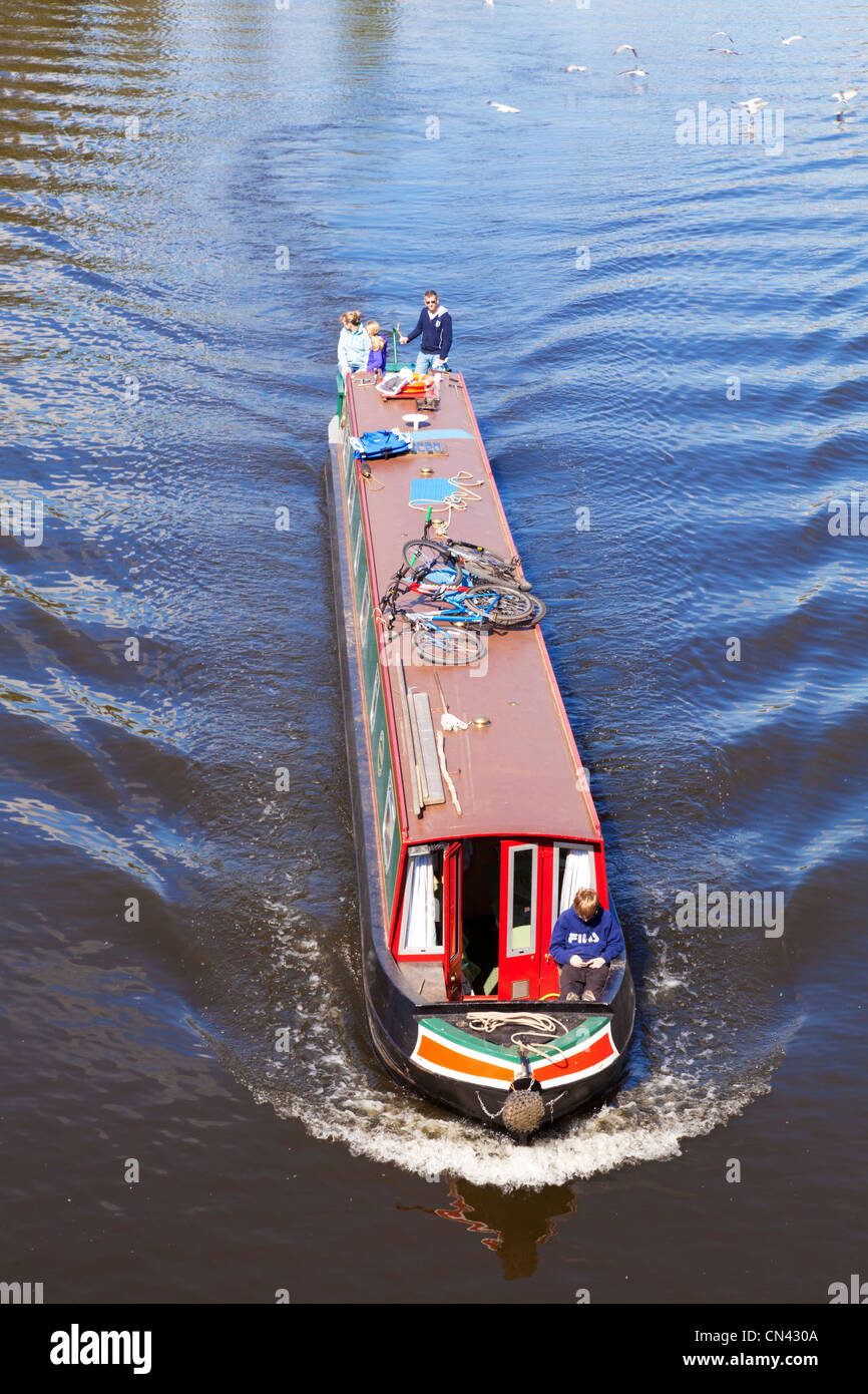 Narrowboat with young family on the River Severn at Worcester, approaching the city centre. Bicycles on the roof. - Stock Image