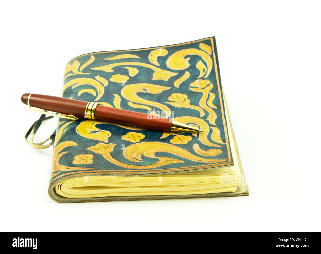 Rosewood pen placed on leather journal. - Stock Image