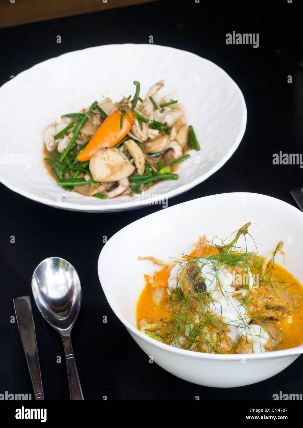 Thai food, yellow curry, kaeng carri, with chicken in the foreground Stock Photo