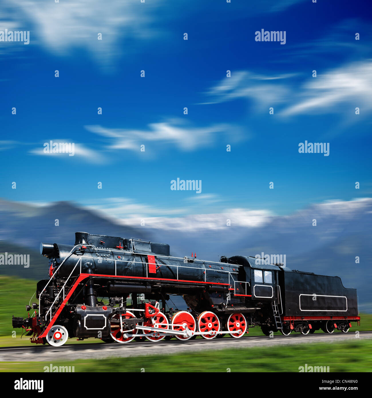 Speeding old locomotive in mountains - Stock Image