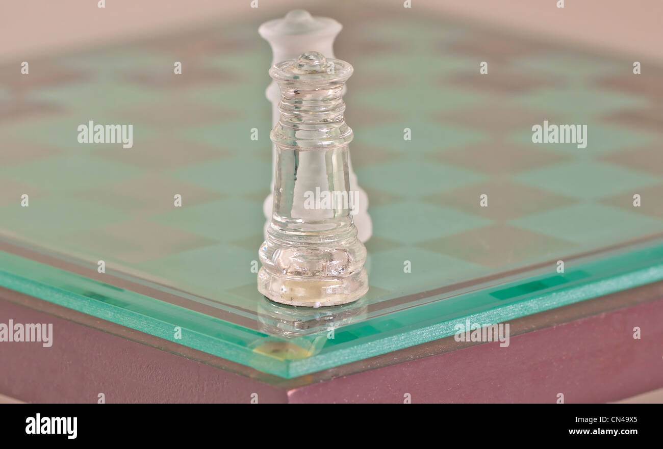 Two glass kings of chess fronting each other - Stock Image