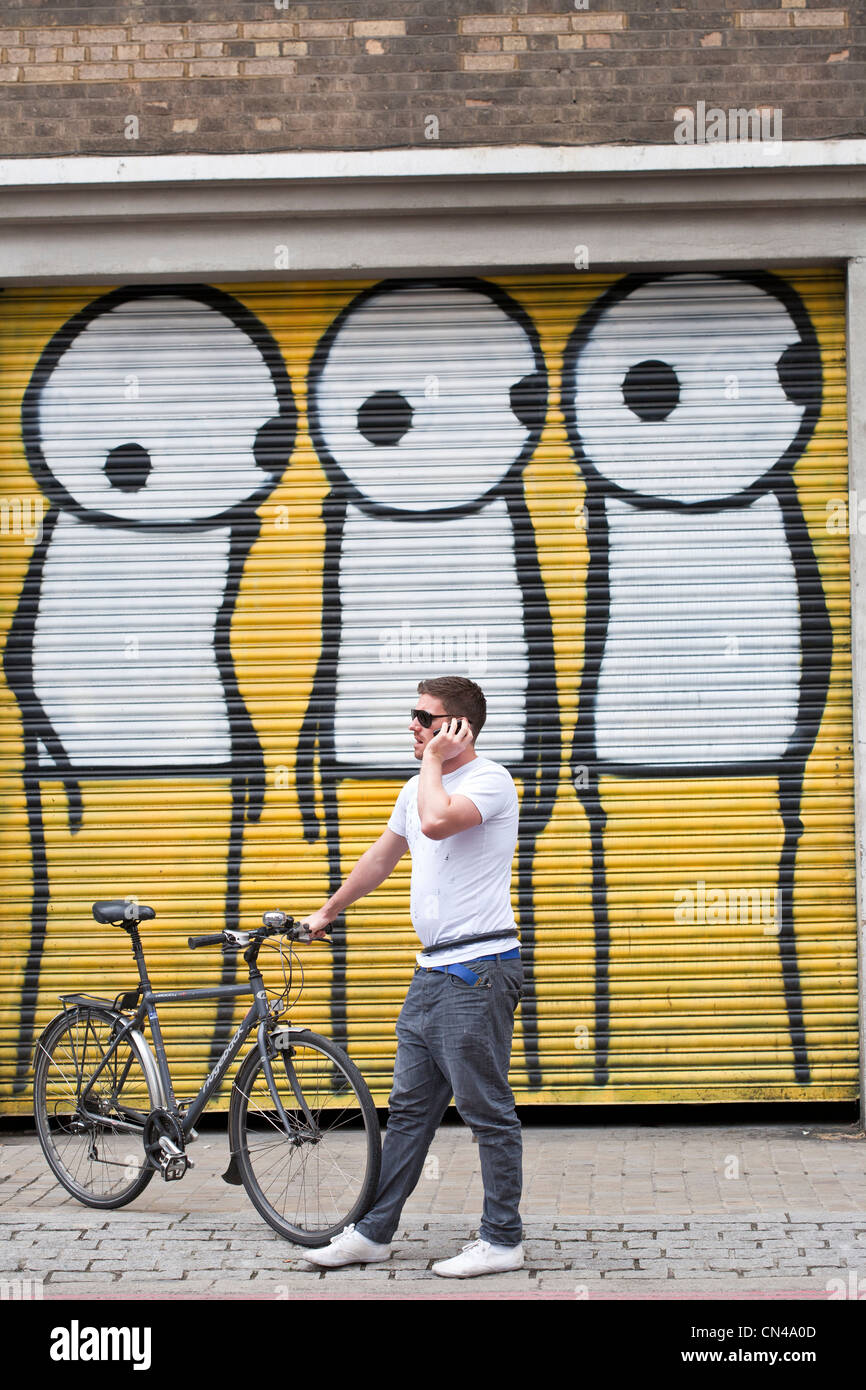 United Kingdom, London, Hackney, Shoreditch, Curtain Road, Mutate Britain, cyclist in front of a graffiti by Stik - Stock Image