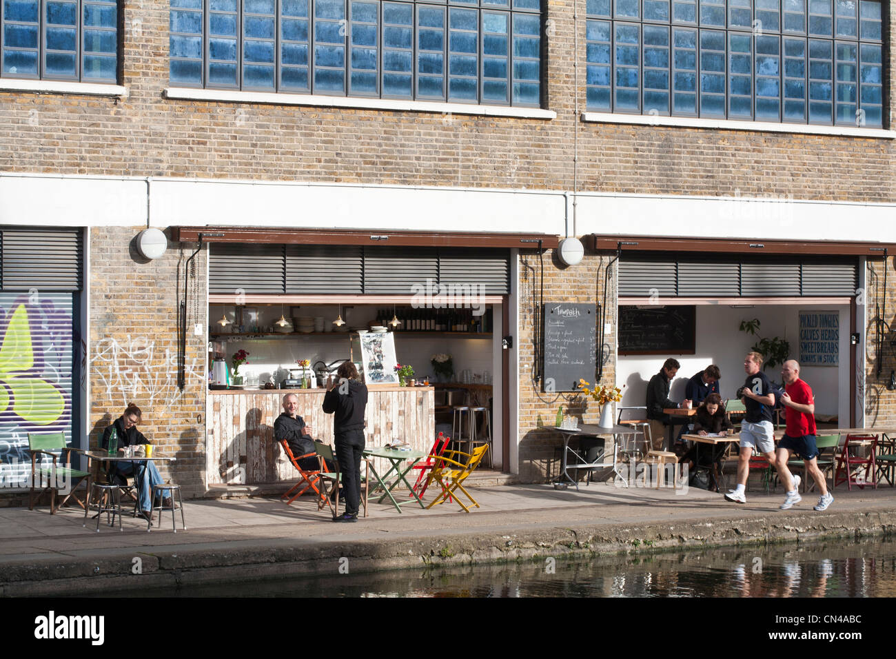 United Kingdom, London, Hackney, Regent's Canal, joggers in front of Towpath cafe open in 2010 by the canal - Stock Image