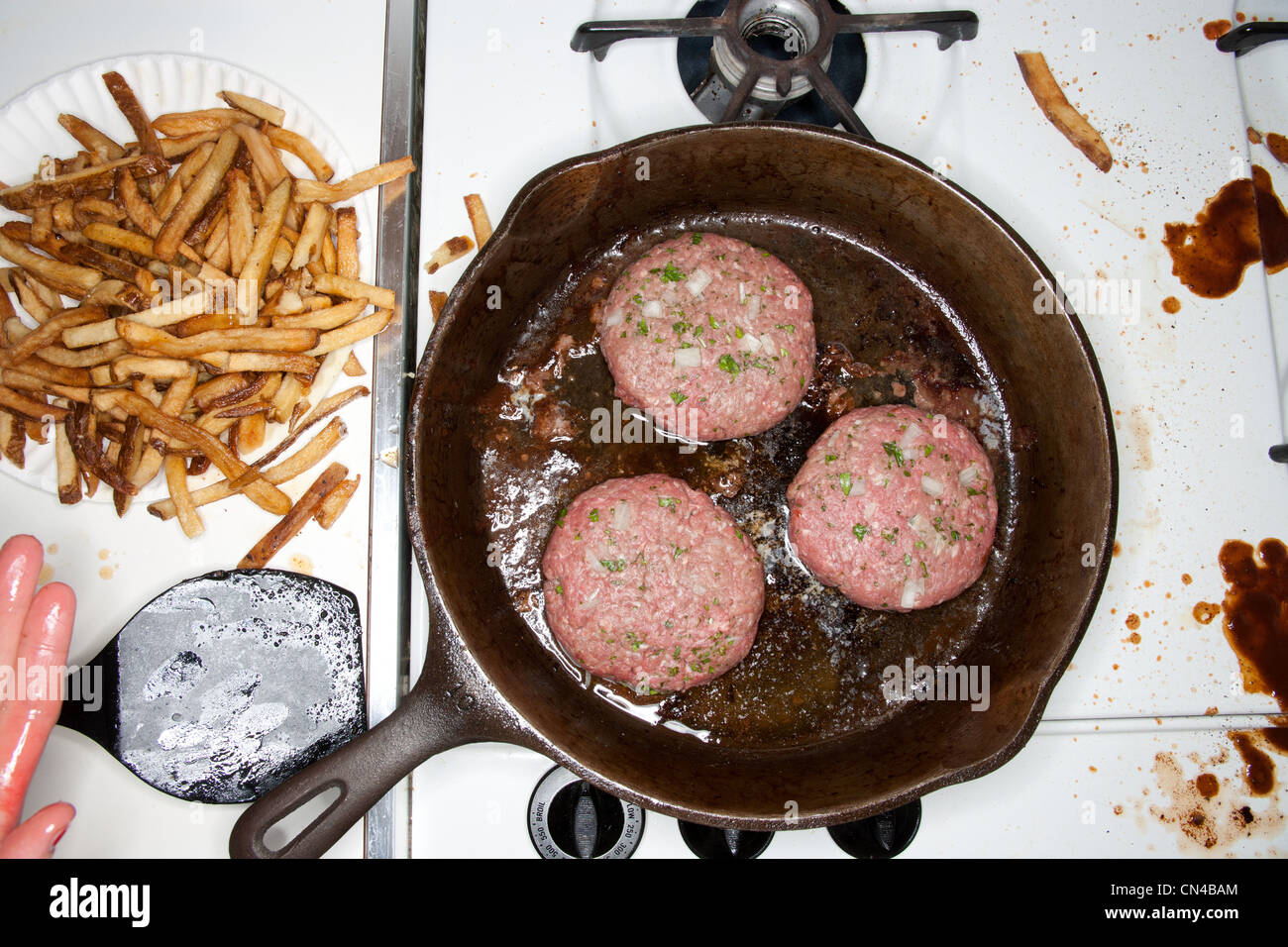 Burgers cooking in a frying pan - Stock Image