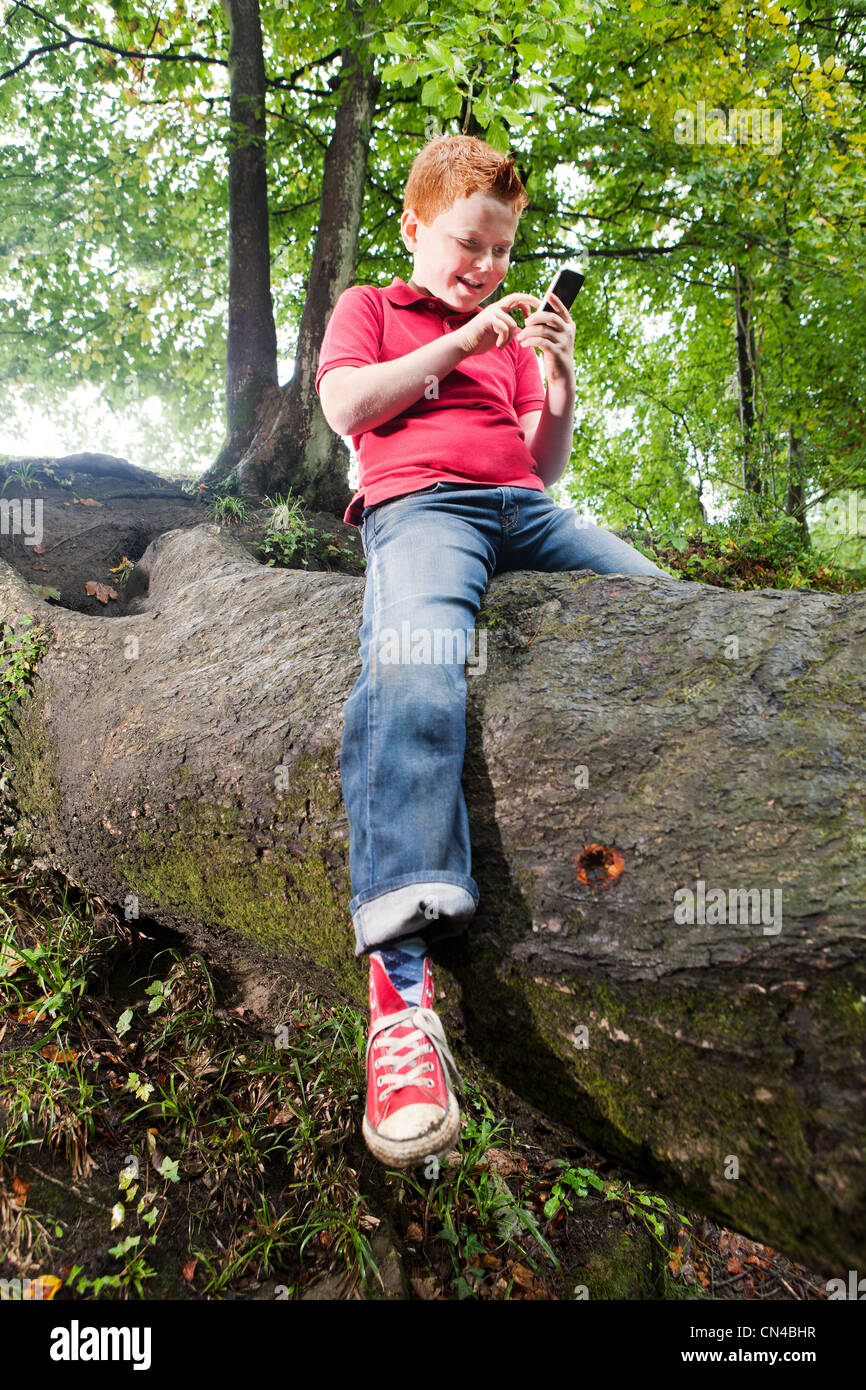 Boy sitting on a tree trunk using a mobile phone - Stock Image