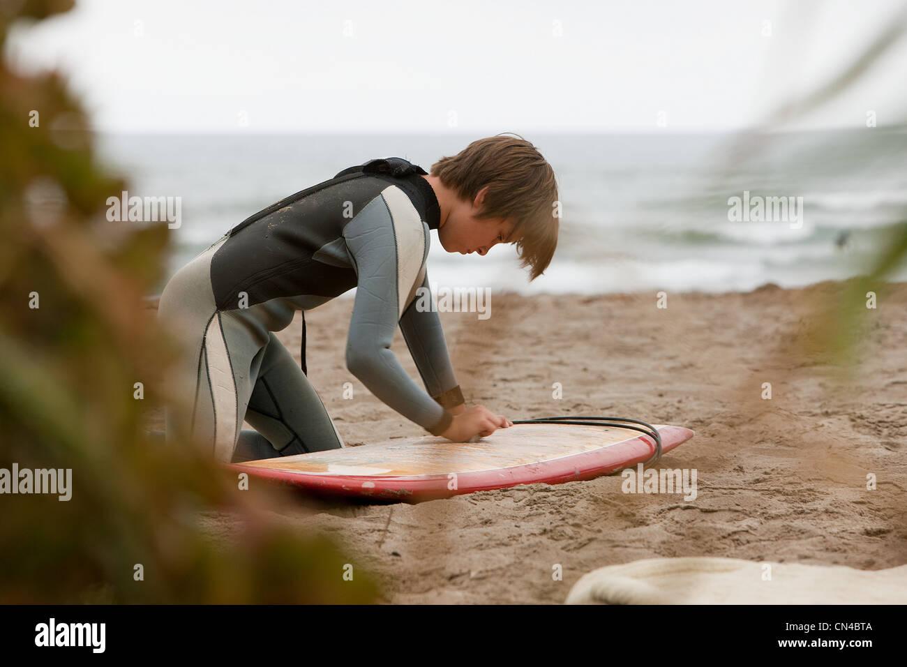 Boy waxing surfboard on beach - Stock Image