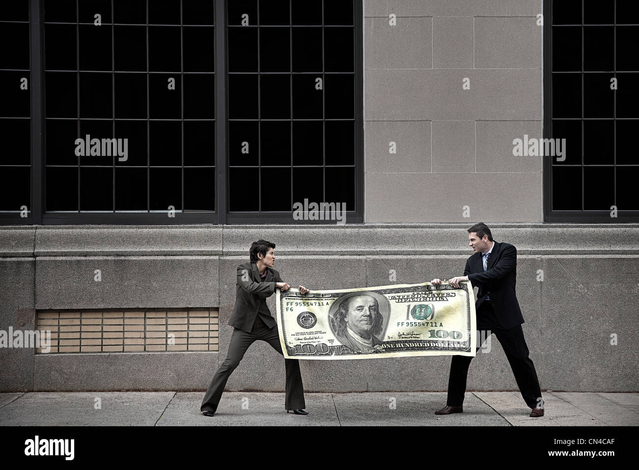Man and woman fighting over large $100 bill Stock Photo