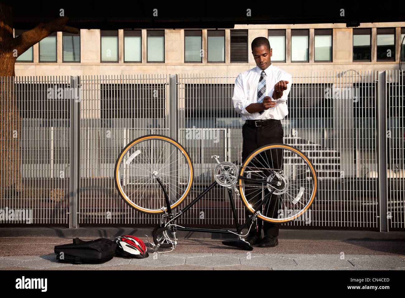 Young businessman rolling sleeves to fix bicycle - Stock Image