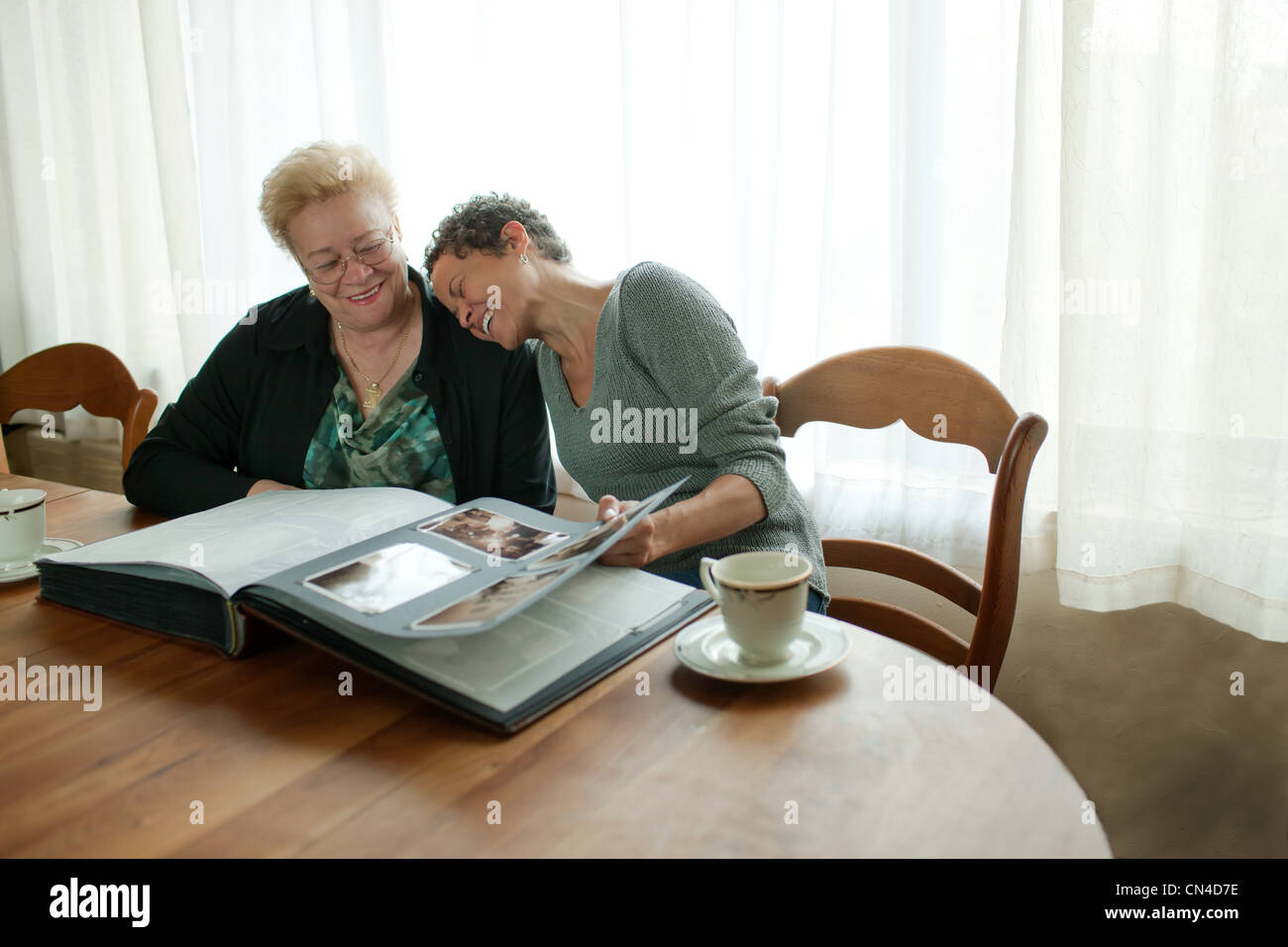 Mother and adult daughter looking through photo album - Stock Image
