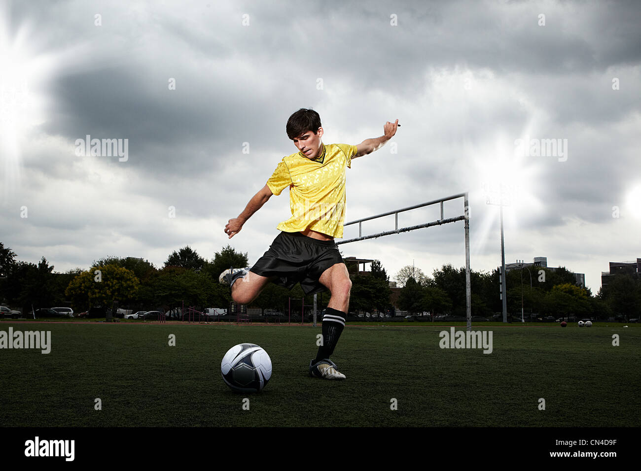 Soccer player about to kick ball on pitch - Stock Image