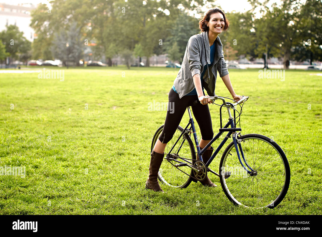 Young woman on bicycle in park - Stock Image