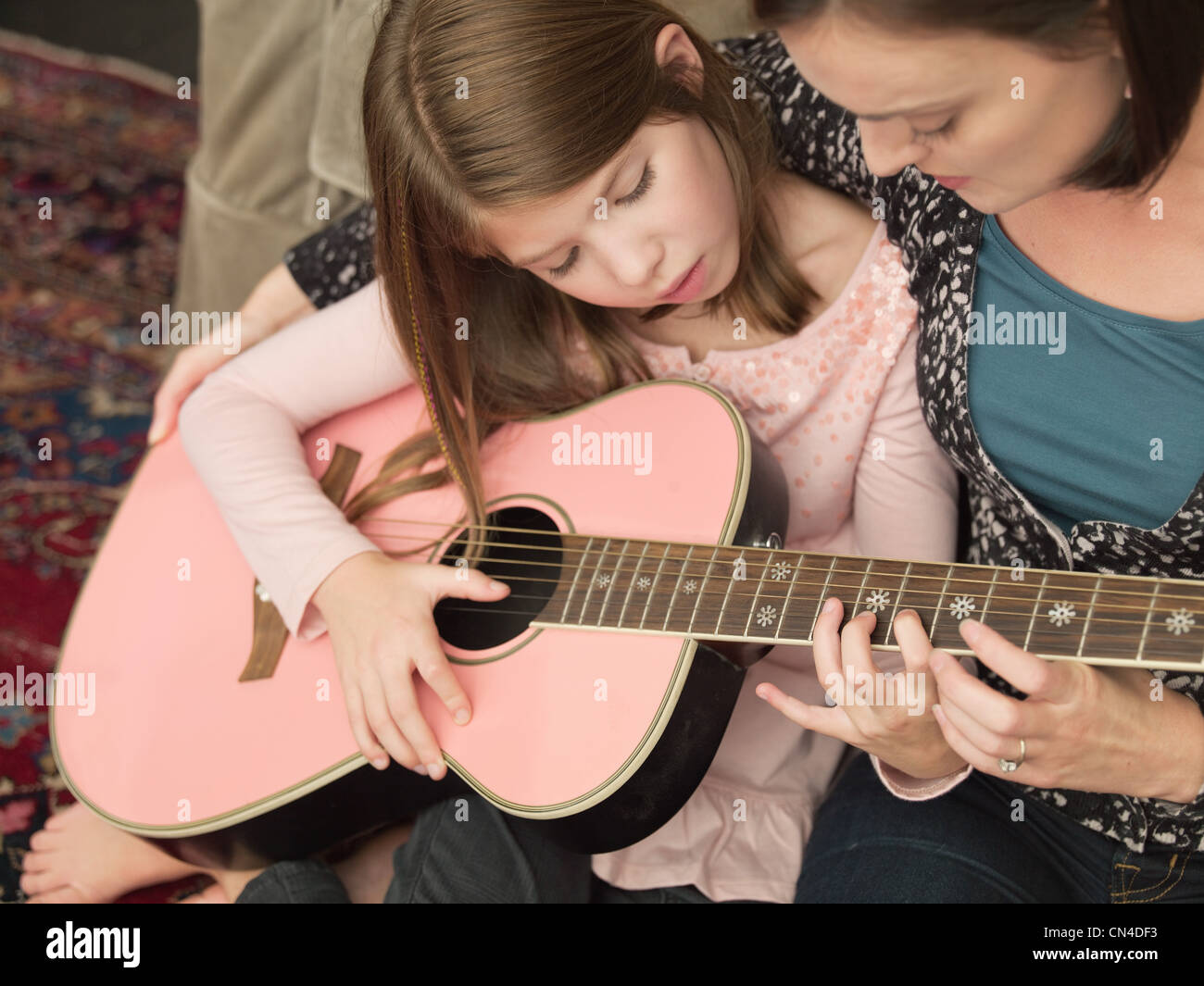 Mid adult woman teaching daughter to play acoustic guitar - Stock Image