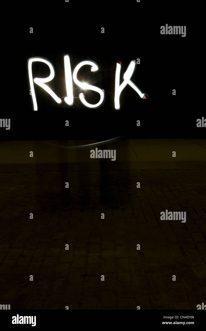 Risk written by light trail at night - Stock Image