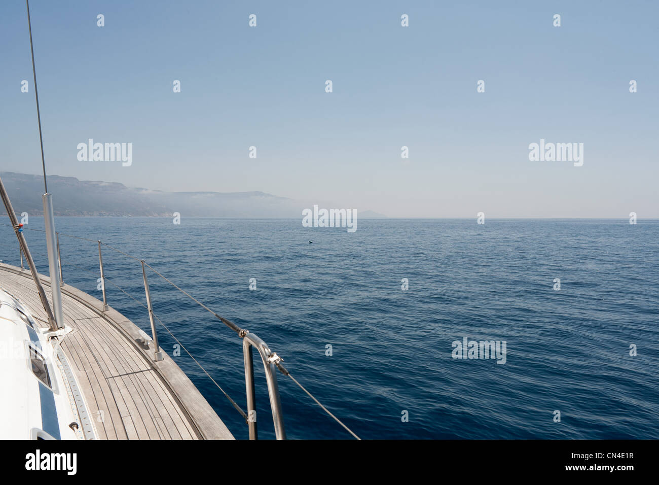 View of the side of a yacht and the Sardinian coast - Stock Image
