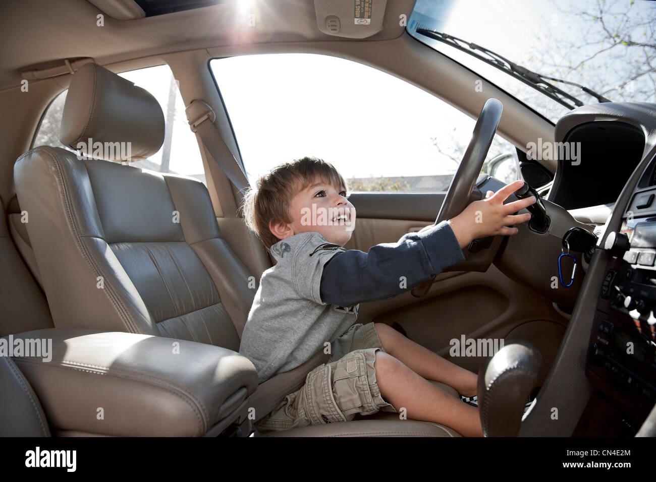 Little boy pretending to drive car - Stock Image