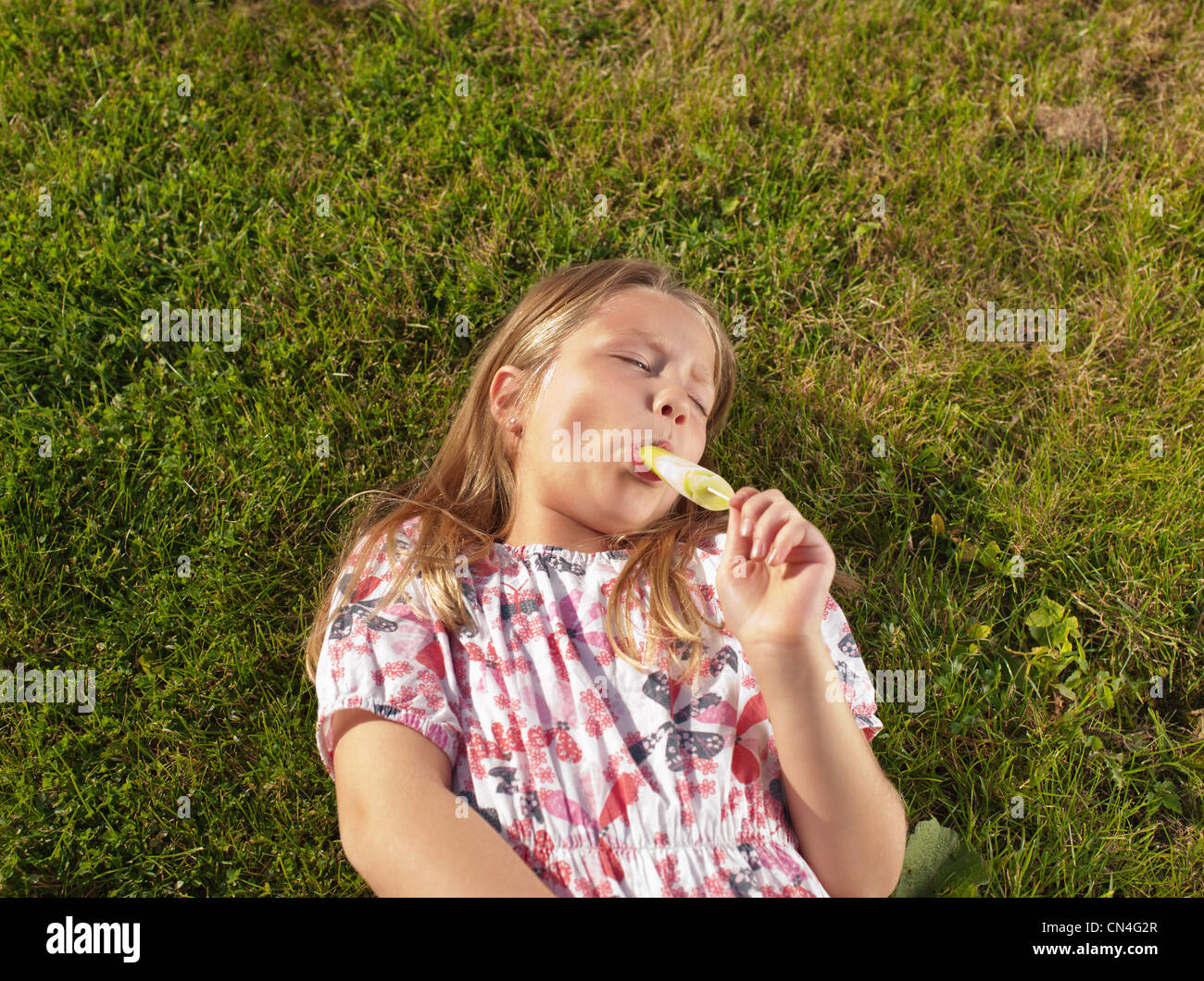Girl enjoying ice lolly on lawn Stock Photo