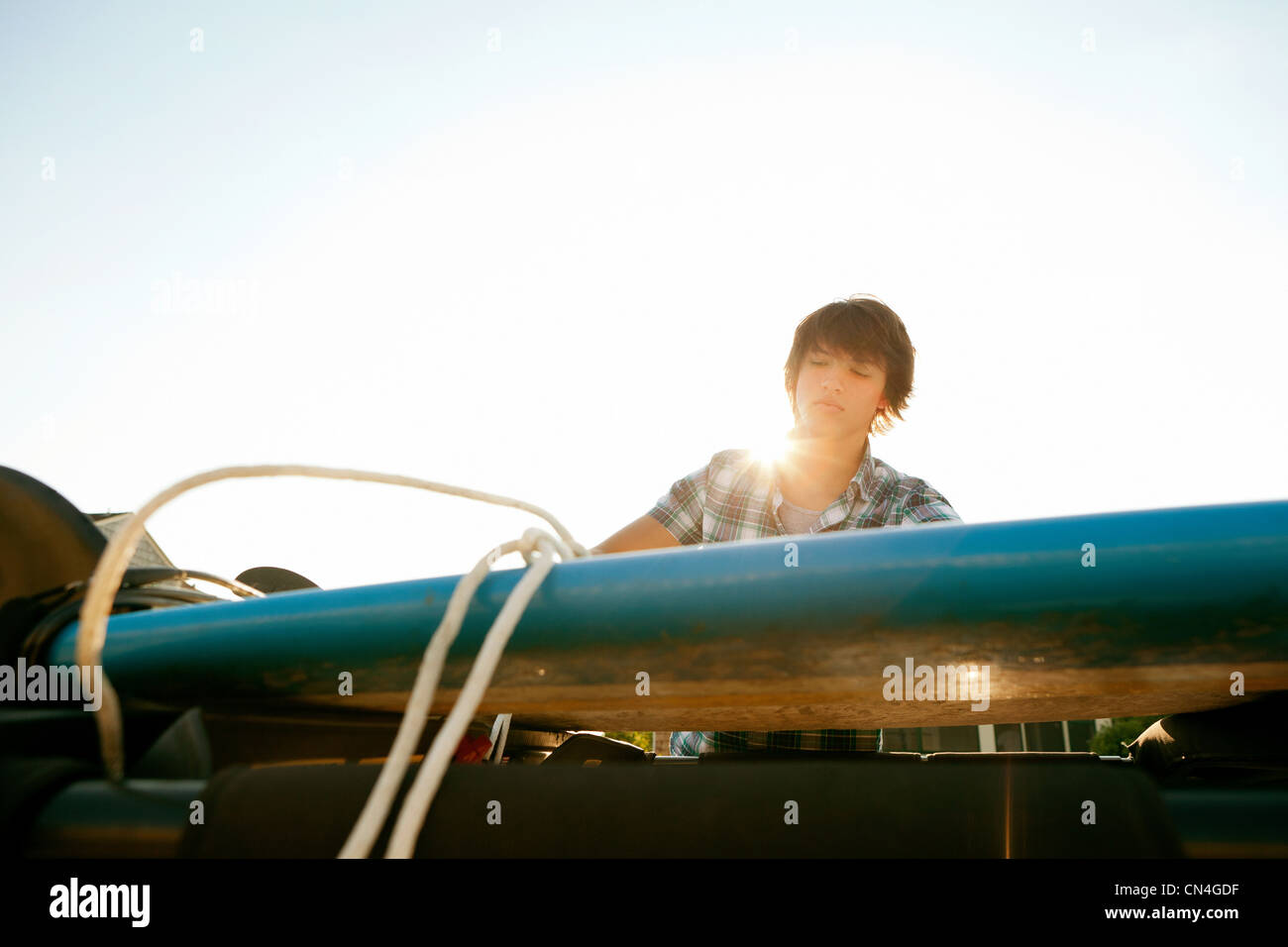Teenager untying his board from roof of jeep - Stock Image