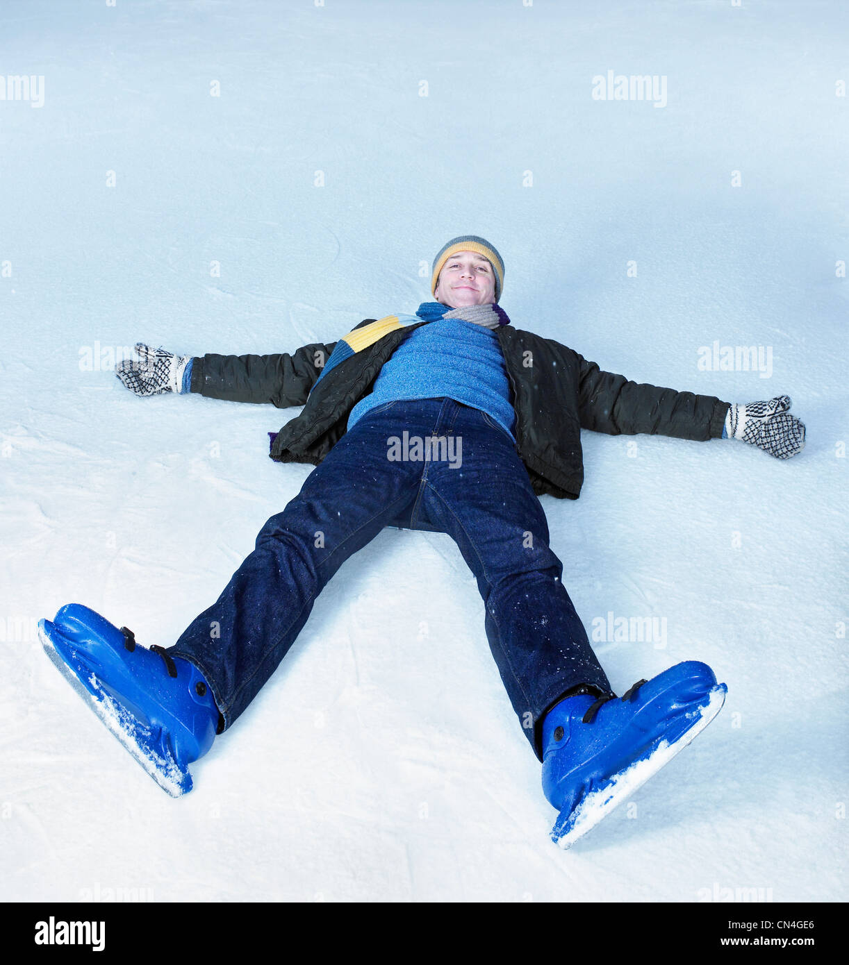 Man lying flat on his back on ice - Stock Image