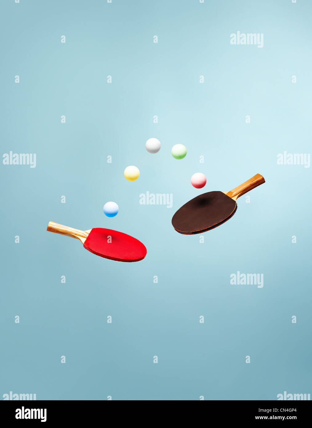 Table tennis bats and balls suspended in the air - Stock Image