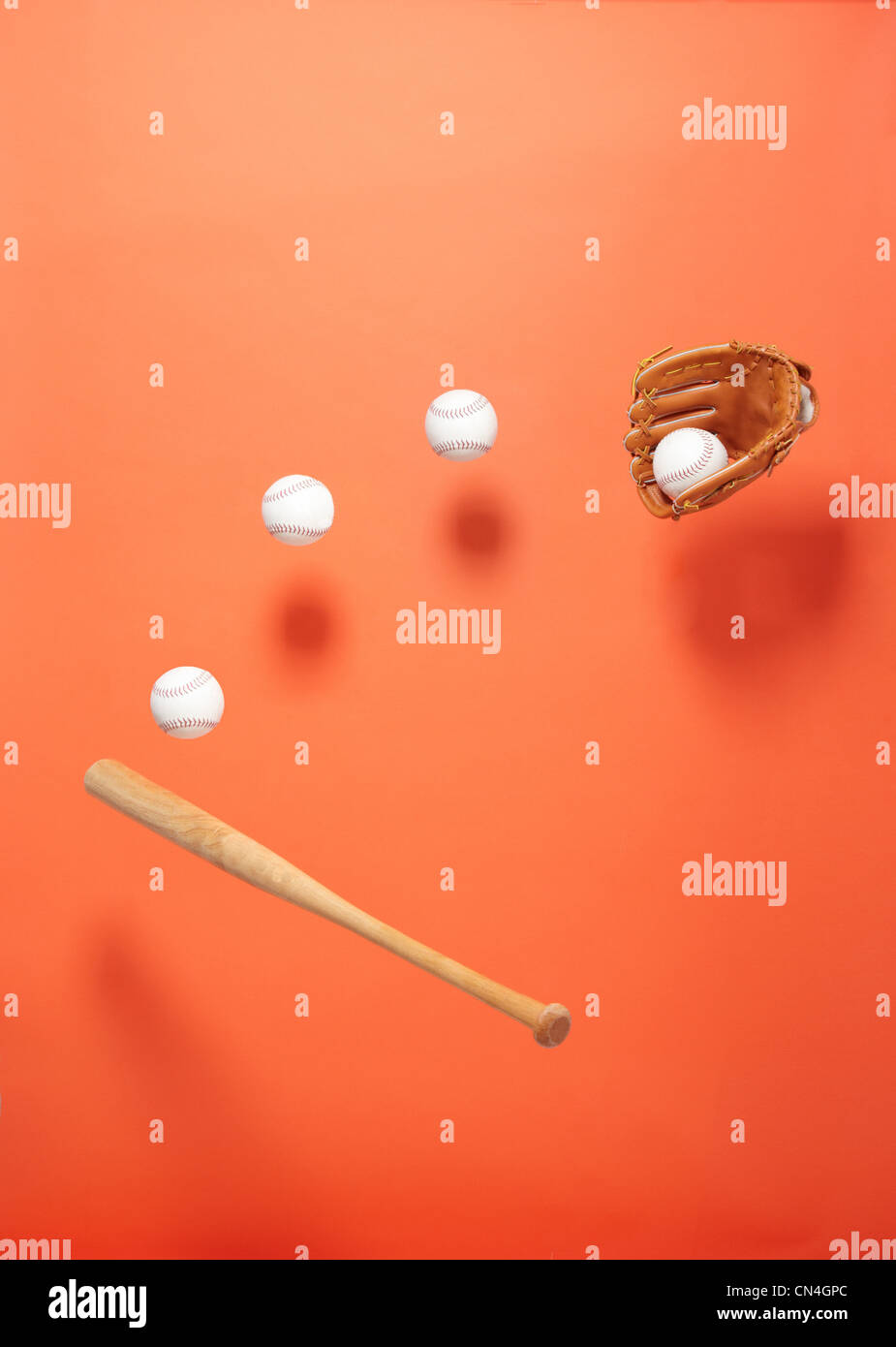 Baseball bat, glove and balls suspended in the air - Stock Image