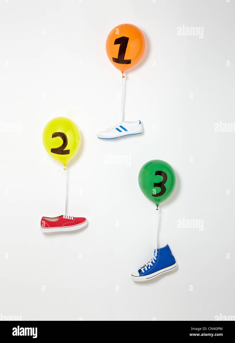 Trainers floating upward suspended by balloons - Stock Image